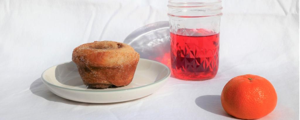 A morning cinnamon roll bun with a glass of refreshing hibiscus tea and a mandarine orange.